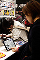 "Visitors read manga on tablets at the Anime Japan 2015 on March 21, 2015 in Tokyo, Japan. Anime Japan 2015 brings together all aspects of the ""anime"" industry offering an opportunity for visitors get close to creators, voice actors, idol groups, and cosplayers, and to learn about the industry. This is the second year that the exhibition is being held at Tokyo Big Sight. Organizers estimated that approximately 100,000 visitors attended in 2014 and similar huge numbers are expected this year. The exhibition is open on March 21st and 22nd. (Photo by Rodrigo Reyes Marin/AFLO)"