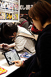 """Visitors read manga on tablets at the Anime Japan 2015 on March 21, 2015 in Tokyo, Japan. Anime Japan 2015 brings together all aspects of the """"anime"""" industry offering an opportunity for visitors get close to creators, voice actors, idol groups, and cosplayers, and to learn about the industry. This is the second year that the exhibition is being held at Tokyo Big Sight. Organizers estimated that approximately 100,000 visitors attended in 2014 and similar huge numbers are expected this year. The exhibition is open on March 21st and 22nd. (Photo by Rodrigo Reyes Marin/AFLO)"""