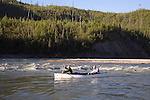 Gary Womeldorff (bow) and Andy Dappen head out from last camp on Kechika River, just above confluence with Liard River.  Muskwa-Kechika Management Area..British Columbia.  Canoe is Clipper Cascade.  Morning