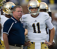 Head coach Brian Kelly talks with quarterback Tommy Rees (11).