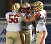 Justin Brown #1 of Half Hollow Hills West, center, gets congratulated by Mike Freda #56, left, and Mike Stone #60 after rushing for a 75-yard touchdown in the first quarter of the Class III Long Island Championship against Plainedge at Shuart Stadium in Hempstead on Saturday, Nov. 24, 2018.