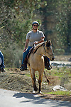 Horse back rider leaving staging area for a  trail ride