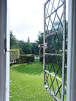 Through an open leaded window a view of the lawn and pleached hornbeam trees in the garden