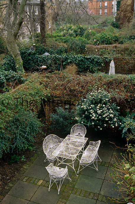 A small patio garden with wrought iron furniture is one of several gardens which back onto each other in this typical London view