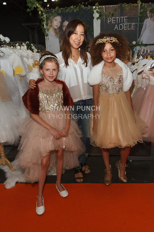 Fashion designer Sam Na poses with child models weraing her Petite Adele collection, for the petitePARADE Spring Summer 2018 fashion show with Children's Club, at Javits Center in New York City, on August 7, 2017.