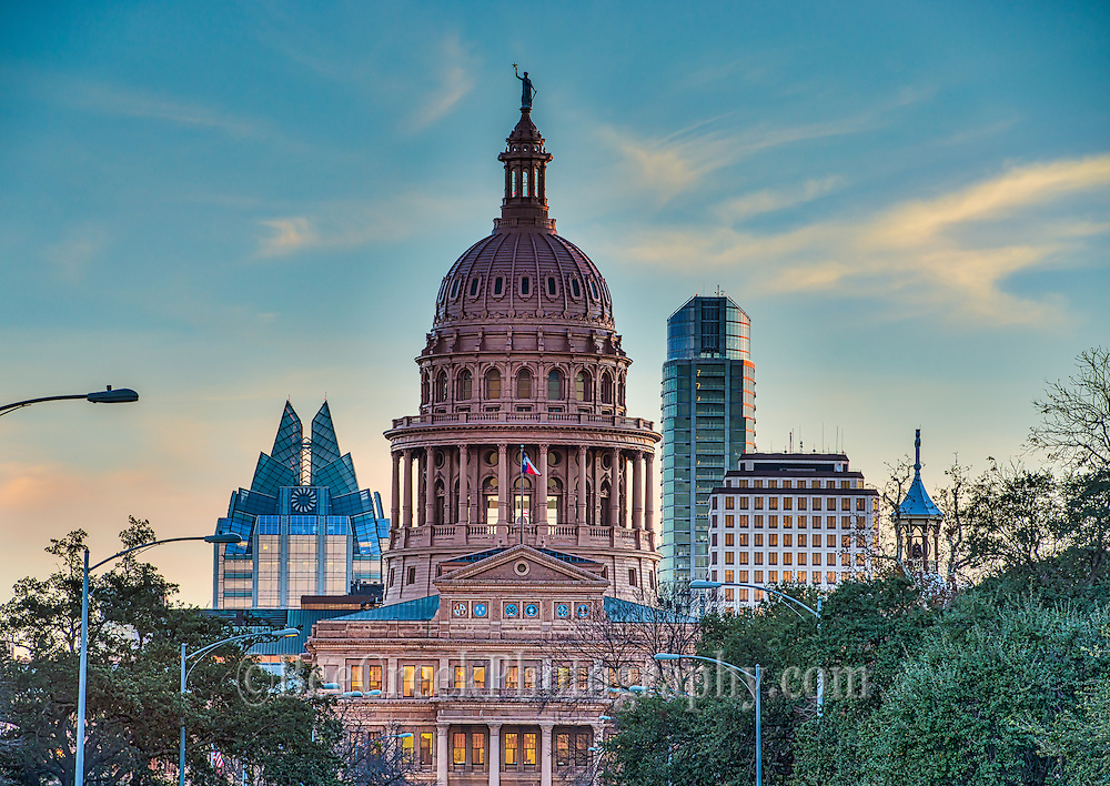 "The Capitol of Texas at sunset in downtown Austin with the city skyline behind it is a stunning view.  You can see the skyscrapers towering behind the Capitol in downtown.   This city photo with the skyscraper in the background as the sun was setting in the sky is a very nice site.  We were able to capture this photo with just a touch of color in the clouds and it cast a nice glow over the Capitol and the two prominently high rise buildings in this city skyline the Frost and Austonian which were visible from this angle The capital style was the Renaissance Revival architecture of the  15th-century Italy.  The Capitol exterior is made of ""sunset red"" granite which really makes it stand out against a blue sky."