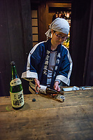 Japan, Okayama Prefecture, Katsuyama. Tsuji Honten Sake factory. Family run for seven generations, brother-sister team of President and Master Brewer. Maiko, master brewer pouring sake. MR