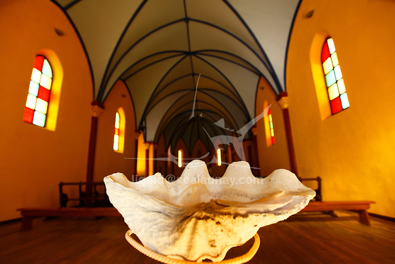 "Interior of the Fayaoue Catholic church on the ouvea island in the Loyalty islands..Ouvéa (local pronunciation: [u?ve.a]) is a commune in the Loyalty Islands Province of New Caledonia, an overseas territory of France in the Pacific Ocean. The settlement of Fayaoué [fa?jawe], on Ouvéa Island, is the administrative centre of the commune of Ouvéa..Ouvéa is made up of Ouvéa Island, the smaller Mouli Island and Faiava Island, and several islets around these three islands. All these lie among the Loyalty Islands, to the northeast of New Caledonia's mainland..Ouvéa Island is one of the Loyalty Islands, in the archipelago of New Caledonia, an overseas territory of France in the Pacific Ocean. The island is part of the commune (municipality) of Ouvéa, in the Islands Province of New Caledonia..The crescent-shaped island, which belongs to a larger atoll, is 50 km (30 miles) long and 7 km (4.5 miles) wide. It lies northeast of Grande Terre, New Caledonia's mainland..Ouvéa is home to around 3,000 people that are organized into tribes divided into Polenesian, Melanesian and Walisian by ethnic descend. The Iaai language is spoken on the island..The two native languages of Ouvéa are the Melanesian Iaai and the Polynesian Faga Uvea, which is the only Polynesian language that has taken root in New Caledonia. Speakers of Faga Uvea have fully integrated into the Kanak society, and consider themselves Kanak..Ouvéa has rich marine resources and is home to many sea turtles, species of fish, coral as well as a native parrot, the Uvea Parakeet, that can only be found on the island of Ouvéa..A large crustacaen called a ""coconut crab"" or crabe de cocotier can also be found on the islands. The large crabs live in palm tree plantations and live solely on a diet of coconuts that they crack open with their powerful claws. They are blue in colour and can grow to several kilos in size. They are a land based species and do not venture into the ocean..Ouvéa is also home to trophy Bonefish that inhabi"