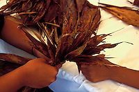 Children weaving dried ti leaves to creates hula costumes and decor