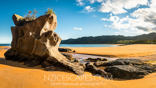 Rock stack on beautiful Totaranui beach on Abel Tasman Coast Track in late afternoon, Abel Tasman National Park, Nelson Region, South Island, New Zealand, NZ
