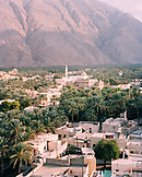 OMAN, cityscape amid trees with mountain in background, elevated view