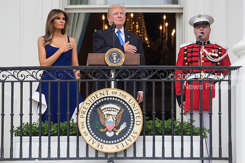 United States President Donald J. Trump and first lady Melania Trump observe the playing of the national anthem from the Truman Balcony on July 4, 2017 in Washington, DC. The president was hosting a picnic for military families  for the July 4 holiday.  <br /> Credit: Zach Gibson / Pool via CNP