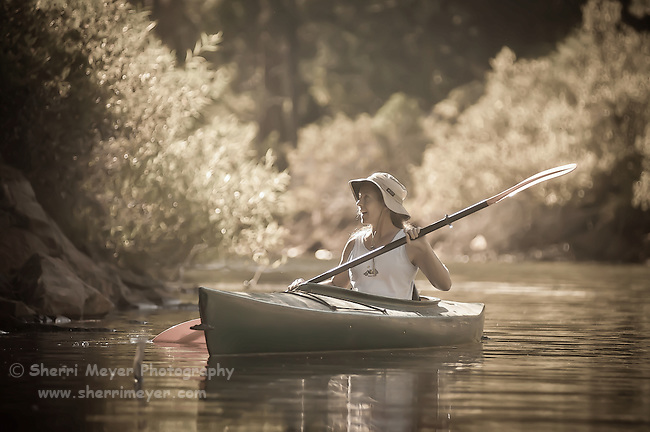 Woman kayaking on Sugar Pine Reservoir, Foresthill, California.