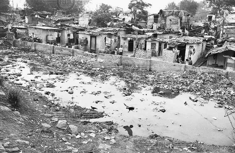 Open sewage next to slum housing.