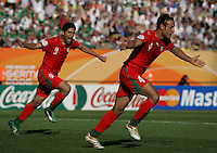 JUNE 11, 2006: Nuremberg, Germany: Iranian defender (4) Yahya Golmohammadi celebrates his goal against Mexico as teammate (9) Vahid Hashemian runs to him at the World Cup Finals at Franken-Stadion in Nuremberg, Germany.  Mexico defeated Iran, 3-1.