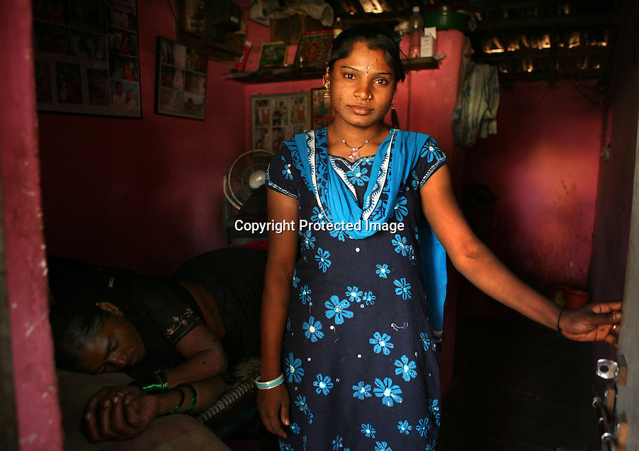 A young sex worker is photographed in her room in the red-light district of Miraj, India. Lying on the bed behind her is an older sex-worker who shares the space with her.  On the walls are photographs from her childhood before she came to Miraj to work. 30% of India's 900 000 sex workers are believed to be children. A girl between the ages of 10 and 12 fetches the highest price.