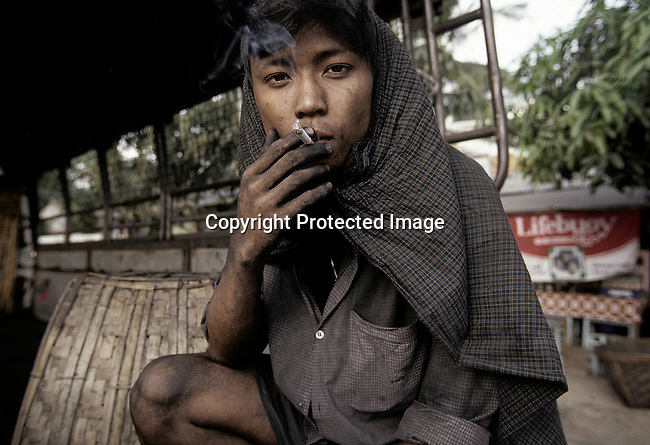 A Burmese young man takes a break while distributing coal from a truck on December 23, 1996 in central Rangoon (Yangon), Burma (Myanmar). A military government took control after they annulled democratic elections in 1988 and many opposition people are in prison. (Photo by: Per-Anders Pettersson)