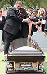 Funeral for Perth Amboy Police Officer Thomas Raji. Funeral at the Alpine Cemetery in Perth Amboy where Officer Raji will be laid to rest. Here Marisol Raji, wife of officer Raji (right) is consoled in front of the casket of her husband. <br /> <br /> METRO<br /> 3173<br /> ON MON AUG 25 ,2008<br /> MARK R. SULLIVAN/CHIEF PHOTOGRAPHER