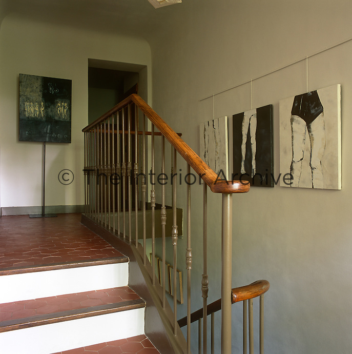 A staircase leads up to a landing area with contemporary paintings hanging on the wall.