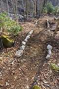 In 2011, Tropical Storm Irene washed out part of the Mt Tecumseh Trail in New Hampshire, and this is the start of the rerouted section of trail in April 2012. After a trail inspection by Forest Service in June 2012 the stone walls on each side of the trail were removed. A defined path had been established and the walls no longer served any purpose. Removing the stones gives the trail a more natural look and feel. This photo shows the trail before the stones were removed.