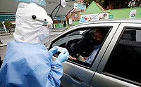 BOGOTA, COLOMBIA - MAY 13:  A nurse prepares to take a sample in a COVID-19 drive-through test point on May 13, 2020 in Bogota. The drive-through test point, the first in Colombia, had a capacity to take 1,400 Covid-19 test a month with a cost of $50 dollars to every patient. (Photo by Leonardo Munoz/VIEWpress via Getty Images)