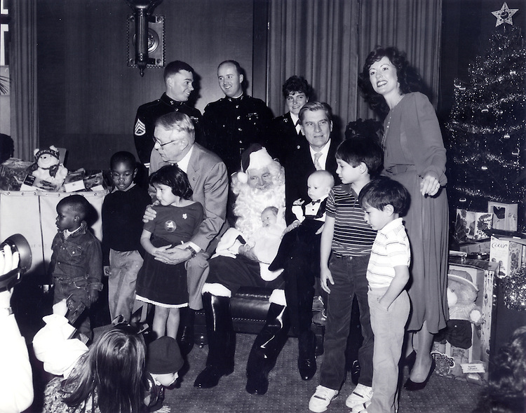 "It was taken in December 1987 at a U.S. Marine Corps Reserve ""Toys for Tots"" event in the Rules Committee hearing room.  The seated Senators from left are Sens. Wendell Ford, Howell Heflin, and John Warner. Senator Warner is holding Austin Caldwell, age 6 months, son of the woman standing, Robin Caldwell, who is still on Senator Warner's staff.."
