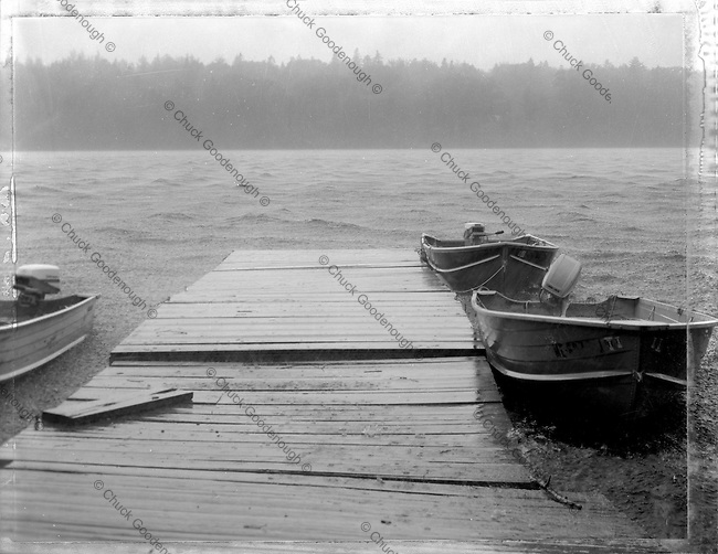Black & White 4x5 Polaroid Photo of a fishing dock in Maine with boats during a rain squall.