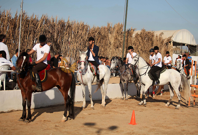 Palestinian horse riders take part in a jumping competition in Gaza city on June 12, 2015. The competition organized by Gaza equestrian club participant by 35 rider from the besieged coastal enclave. Photo by Ashraf Amra