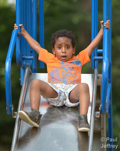 Three-year old Youel, a resettled refugee from Eritrea, faces a moment of decision on a slide in a playground in Durham, North Carolina. <br /> <br /> The boy and his mother were resettled in Durham by Church World Service, which resettles refugees in North Carolina and throughout the United States.<br /> <br /> <br /> Photo by Paul Jeffrey for Church World Service.