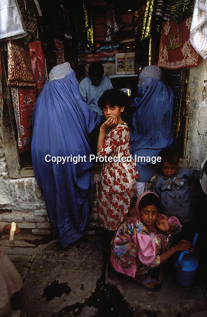 COAFGHA35007.Country. Afghanistan. Herat. Covered woman with girls in a market. They are not allowed to work or go to school..©Per-Anders Pettersson/iAfrika Photos