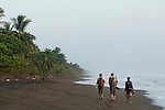 Jaguar (Panthera onca) biologists, Stephanny Arroyo-Arce, Ian Thomson, and Jizel Miles, walking down beach to check for predated sea turtles, Coastal Jaguar Conservation Project, Tortuguero National Park, Costa Rica