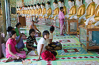Myanmar, Burma.   Umin Thounzeh, Buddhist Shrine on Sagaing Hill, near Mandalay.  Women visiting, praying.
