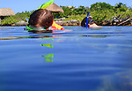 Father and daughter snorkeling in lagoon