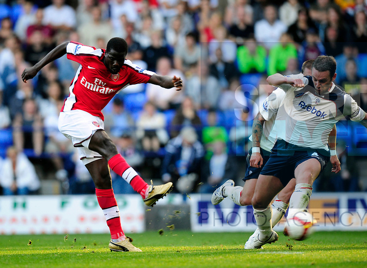 Emmanuel Eboue of Arsenal shoots past Bolton Wanderers Kevin Nolan