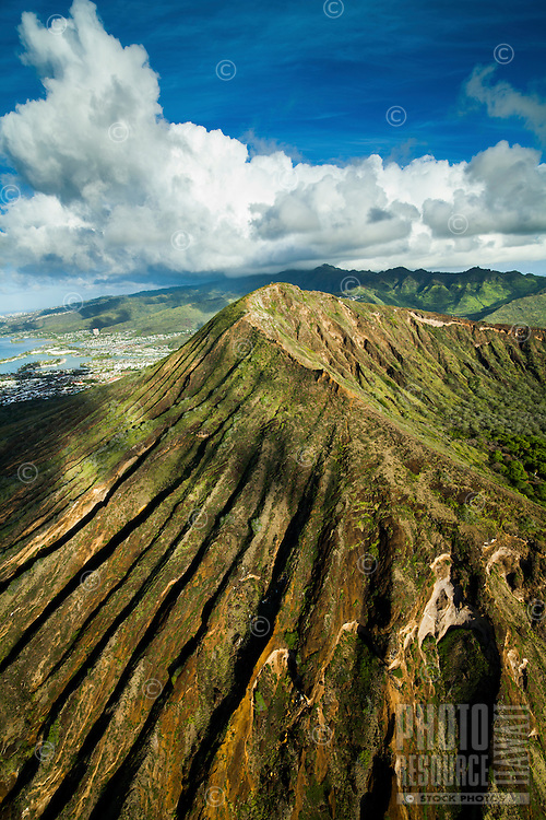 An aerial view of O'ahu's Koko Crater at sunrise, with the Ko'olau Range in the distance.