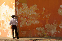 Man standing in front of a colorful wall in Antigua, Guatemala. Antigua is a UNESCO World heritage site....