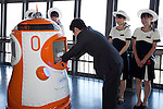 """August 01 2012, Tokyo, Japan - The president of Tokyo Tower, Shin Maeda gives the employee ID to the new robot guide. Tokyo Tower implemented the new robot guide which name is """"Tawabo"""", the first indoor robot guide in Japan. It can speak Japanese, English, Chinese and Korean, it weights 200kg and it is 160cm tall."""