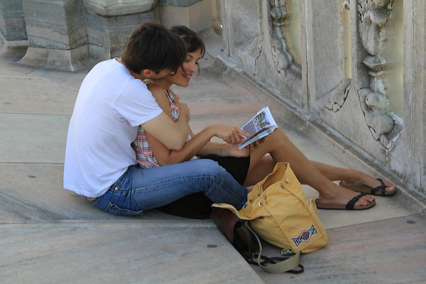 Italy, Milan.  <br /> Work fast, that's all I can say. Photo buyers do seem to like photos with people pointing. <br /> While on the roof of the Duomo Cathedral, a couple reads their guidebook. A fairly generic travel photo.