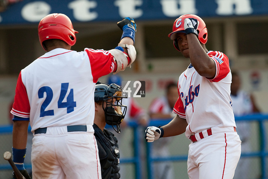 27 September 2009: Alfredo Despaigne of Cuba is congratulated by Frederich Cepeda as he scores after a record 11th home run to cut the margin to 10-6 in the eighth inning during the 2009 Baseball World Cup gold medal game won 10-5 by Team USA over Cuba, in Nettuno, Italy.
