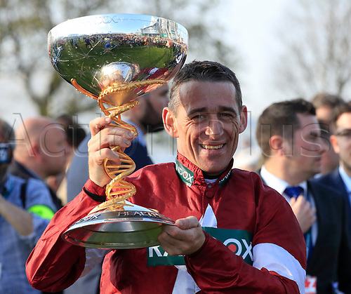 14h April 2018, Aintree Racecourse, Liverpool, England; The 2018 Grand National horse racing festival sponsored by Randox Health, day 3;  The winning jockey Davy Russell celebrates winning the Grand National by holding the trophy aloft