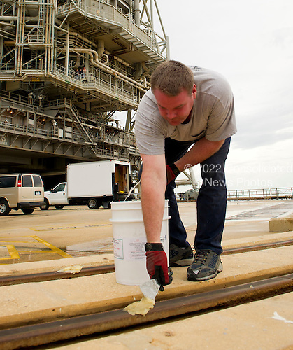 Launch pad worker Chris Cassidy lays down grease on the tracks of the rotating service structure (RSS) on launch pad 39a prior to the RSS being rolled back to reveal the space shuttle Atlantis on Thursday, July 7, 2011 at the NASA Kennedy Space Center in Cape Canaveral, Florida.  Space shuttle Atlantis is set to liftoff Friday, July 8, on the final flight of the shuttle program, STS-135, a 12-day mission to the International Space Station.  .Mandatory Credit: Bill Ingalls / NASA via CNP