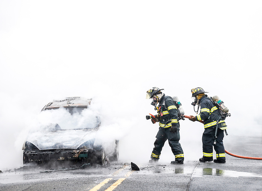 MANASQUAN, NJ — April 1, 2016 — Manasquan firefighters Kevin McCredie and Tom Schofield knock down flames from a 2000 Ford Focus that was fully engulfed at about 9:40am on Broad Street, here. The driver of the vehicle was not injured.  photo by Andrew Mills