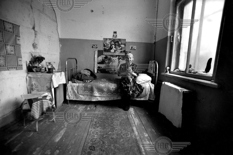 © Heidi Bradner / Panos Pictures..2001 Spring     ..An elderly Russian pensioner, left homeless and alone, living in an abandoned room in a previous old folks home in Grozny. She worked in the Grozny train station for 23 years selling tickets and now she has adorned her walls of her room with cat posters and has adopted three cats.  Many Russian elderly are in Grozny, having few relatives and big families, they are often live on their own.  ..