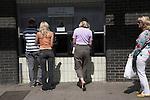 People using ATM cash machine Britain