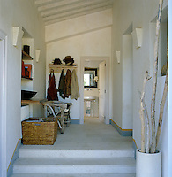The entrance hall has an antique rustic chair and a neat storage area for coats and hats