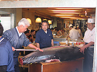 Sushi masters carving a tuna at Tsukiji Fish Market, the largest fish market in the world.