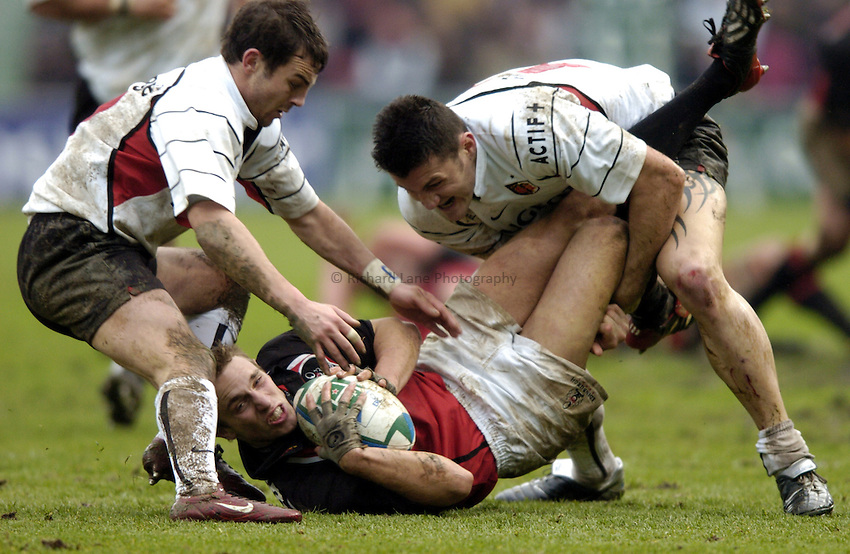 Photo: Richard Lane..Edinburgh Rugby v Stade Toulouse. Heineken Cup. 31/01/2003..Mike Blair is tackled by Jean Baptiste Elissalde and Cedric Desbrosse.