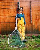 USA, Alaska, Redoubt Bay, a young woman fishing guide holds a fishing net, Redoubt Bay Lodge