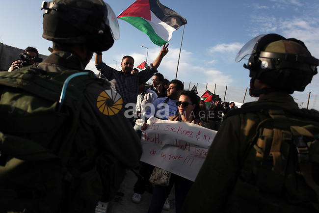 "A woman holds up a sign that reads, ""In Sickness and in health.. until Israel do us part"", as Israeli soldiers prevent the progress of a symbolic wedding party towards the Israeli constructed controversial separation barrier close to the Israeli manned checkpoint of Hezma in the Israeli occupied West Bank, between Jerusalem and the city of Ramallah on March 9, 2013. The ceremony was organized by Palestinians to denounce what they call the ""racist laws that prohibit the reunification of families"". In January 2012, the Israeli Supreme Court endorsed a law banning Palestinians married to Israeli Arabs from obtaining Israeli citizenship or residing in Israel. Photo by Issam Rimawi"