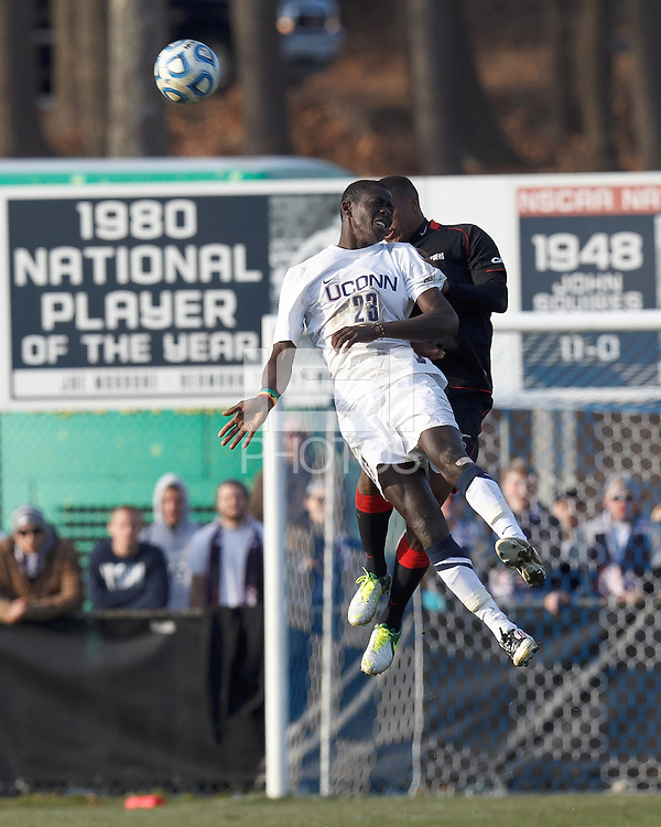 University of Connecticut forward Mamadou Doudou Diouf (23) and Northeastern University defender Ambry Moss (3) battle for head ball. .NCAA Tournament. University of Connecticut (white) defeated Northeastern University (black), 1-0, at Morrone Stadium at University of Connecticut on November 18, 2012.